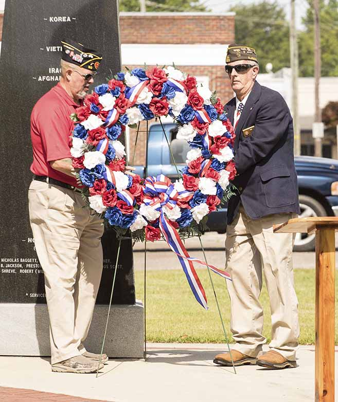 Commander Dave Graham, left, and Commander Billy Gates place the wreath at the monument.